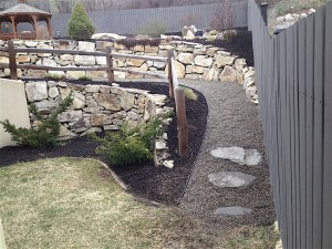 uphill path of rock with retaining wall and a custom fence