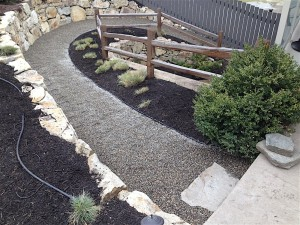 landscaped path with crush rock, a retaining wall and a custom wood fence