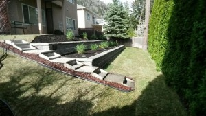 backyard landscape with retaining walls and brick stairs