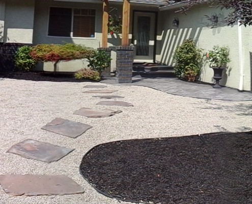 front yard newly landscaped with bark mulch, trees and shrubs
