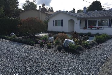 Wide angle showing a newly landscaped front yard edged out with shrubs and bark mulch