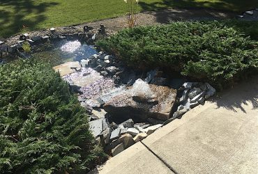 Backyard waterfall designed with landscaping rocks and shrubs